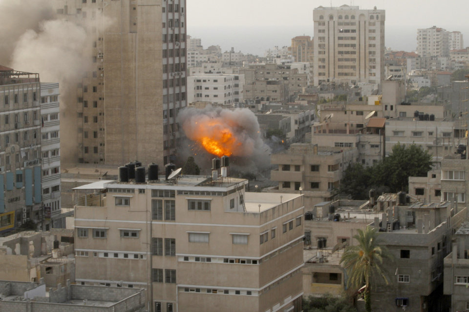 Photo -   Smoke and fire are seen from an explosion by a high rise housing media organizations in Gaza City, Monday, Nov. 19, 2012. It's the Israel's military second strike on the building in two days. The Hamas TV station, Al Aqsa, is located on the top floor. (AP Photo/Hatem Moussa)