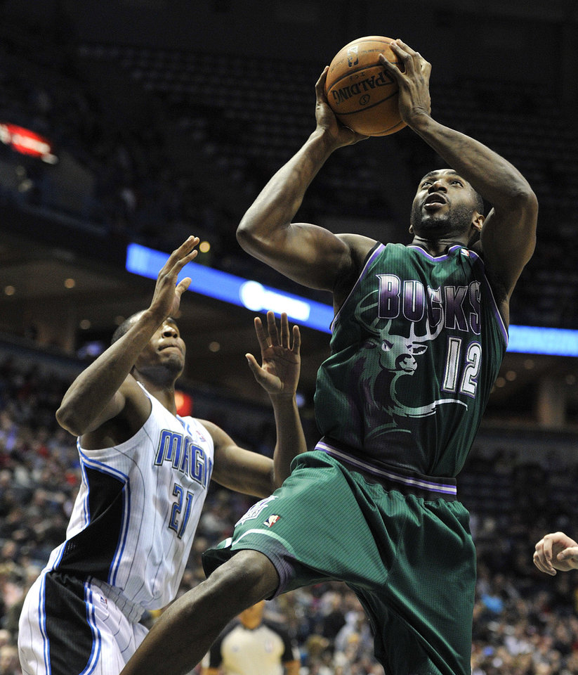 Orlando Magic's Moe Harkless (21) defends as Milwaukee Bucks' Luc Richard Mbah a Moute (12) drives to the basket during the second half of an NBA basketball game on Saturday, Feb. 2, 2013, in Milwaukee. (AP Photo/Jim Prisching)