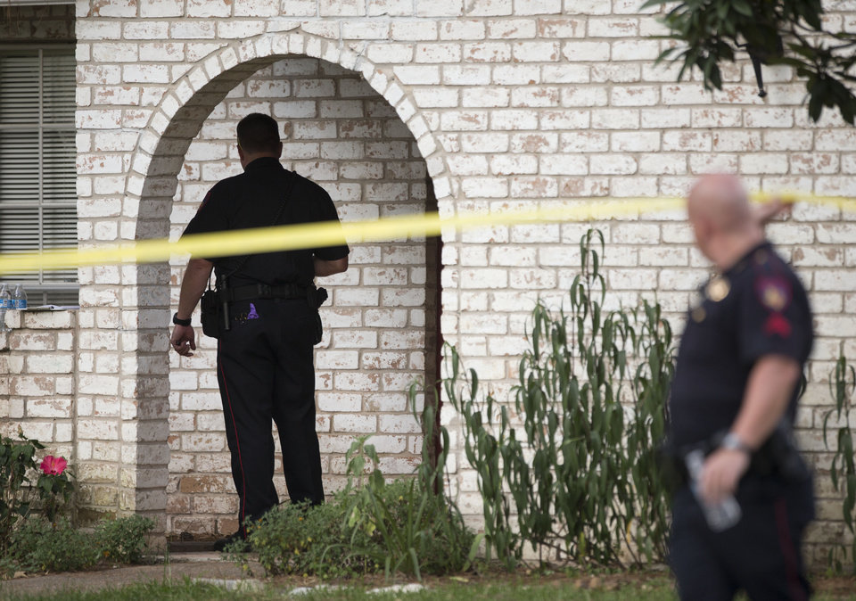 Photo - Law enforcement officers investigate the scene of a shooting Wednesday, July 9, 2014, in Spring, Texas. A Harris County Sheriff's Office statement says precinct deputy constables were called to a house about 6 p.m. Wednesday and found two adults and three children dead. Another child later died at a hospital. (AP Photo/Houston Chronicle, Brett Coomer)