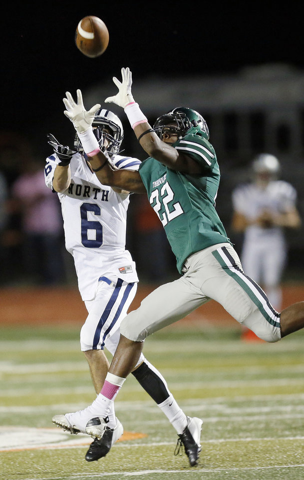 Photo - Norman North's Adim Chukwurah (22) deflects a pass intended for Edmond North's Robert Secrets (6) during a high school football game between Edmond North and Norman North in Norman, Okla., Thursday, Oct. 11, 2012. Photo by Nate Billings, The Oklahoman