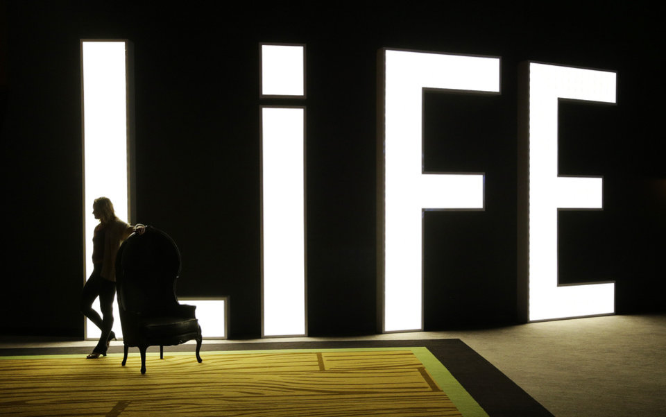 Photo - In this photo taken on Aug. 20, 2014, a woman stands in front of a sign for Life Nightclub in the SLS Las Vegas in Las Vegas. The hotel and casino, formally known as the Sahara, has gone through extensive renovations is scheduled to open this weekend. (AP Photo/John Locher)
