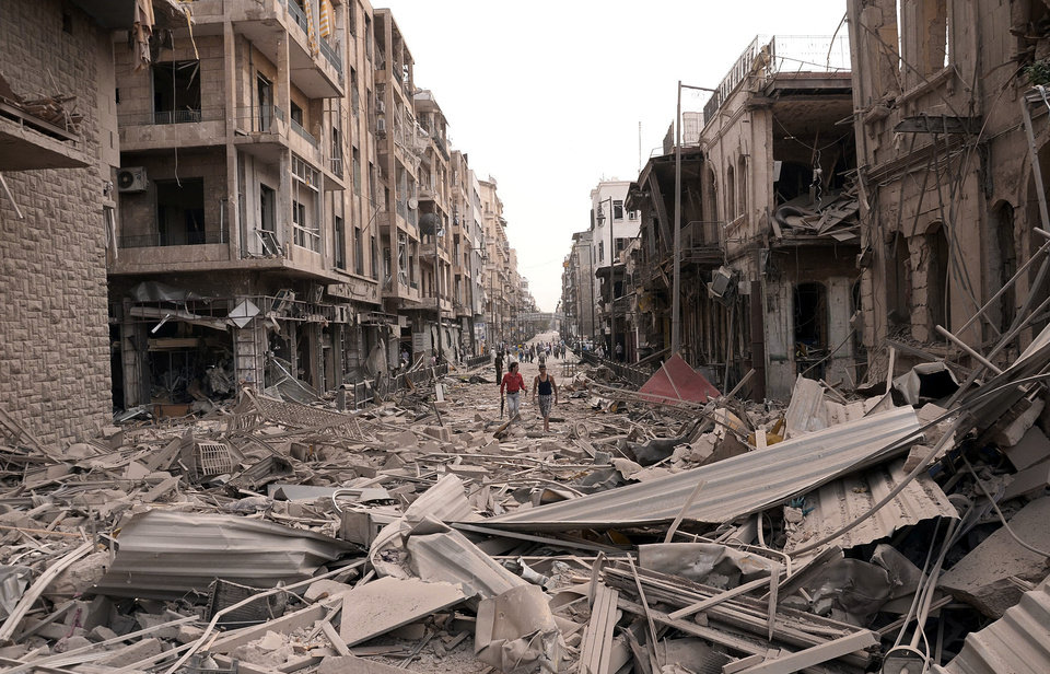 Photo -   In this photo released by the Syrian official news agency SANA, Syrian men walk at a street between destroyed buildings where triple bombs rocked at the Saadallah al-Jabri square, in Aleppo city, Syria, Wednesday Oct. 3, 2012. Three powerful explosions rocked the main square in a government-controlled central district of Aleppo on Wednesday, the Syrian state-run TV said. Activists reported multiple casualties and heavy material damage. (AP Photo/SANA)