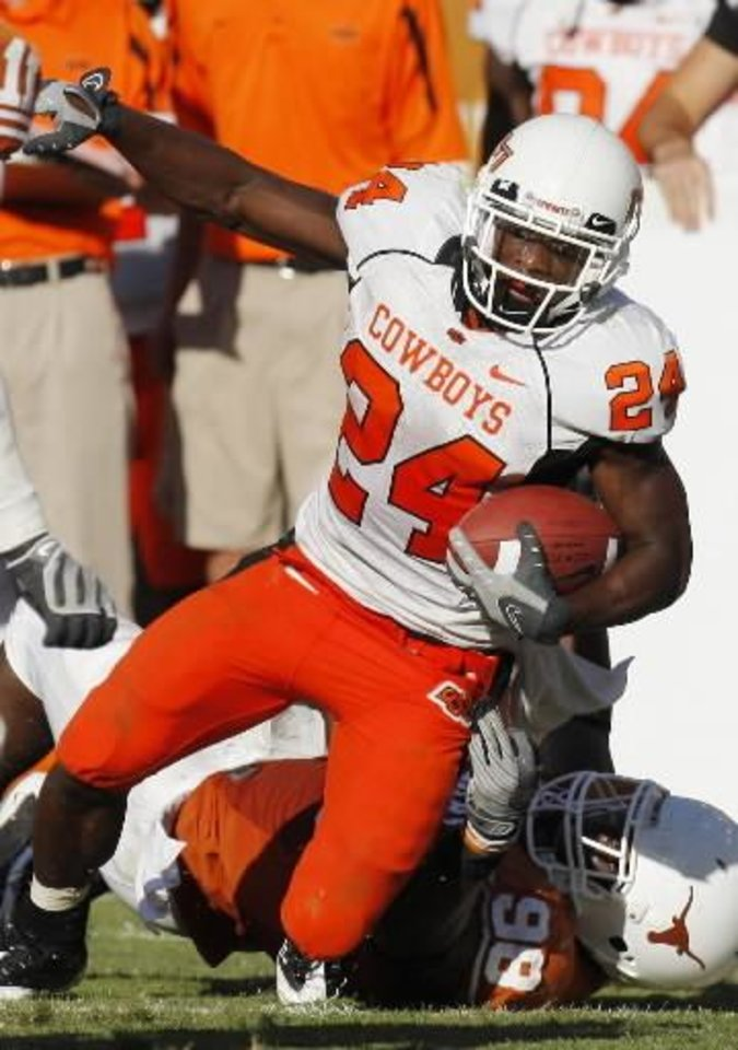 Kendall  Hunter is pulled down by Brian Orakpo as Oklahoma State University (OSU) plays the University of Texas (UT) at Darrell K. Royal-Texas Memorial Stadium at Joe Jamail Field in Austin, Texas on Saturday October 25, 2008. By Doug Hoke, The Oklahoman