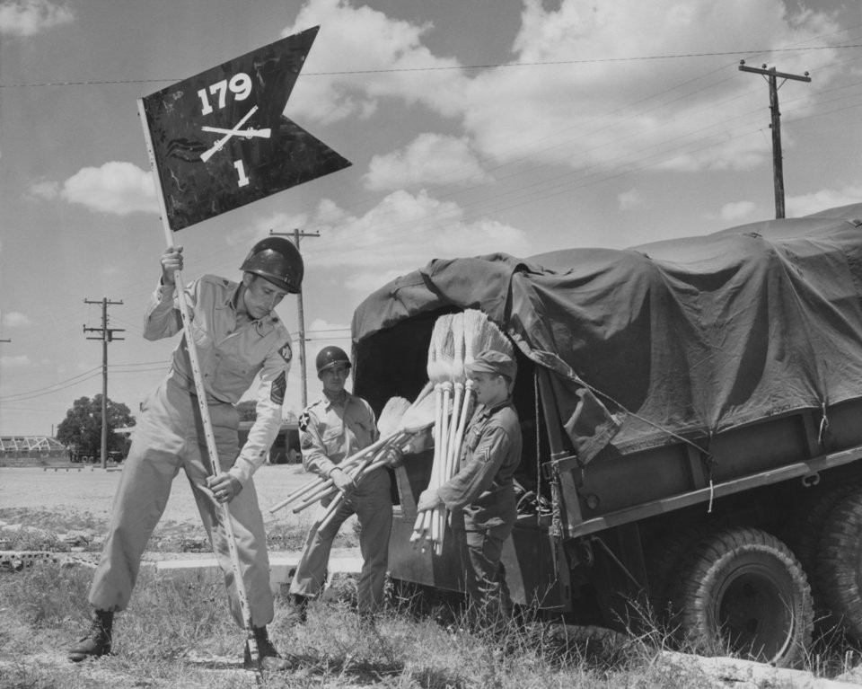 """Photo - Directions were no problem Sunday when members of the 45th division rolled into North Fort Hood for summer camp.  Each unit knew just where to go, thanks to early arriving Thunderbirds who had each company and battery area well marked and spruced up.  Here Sgt. 1-c Irvin Statton plants the guidon of the 179th Infantry regiment's first battalion, while Sgt. 1-c Max Dull, left, and Cpl. Carol Hardwick break out the brooms.  all are from El Reno.""""  Staff photo by George Tapscott, dated 08/06/1955.  Published in The Daily Oklahoman 08/08/1955."""
