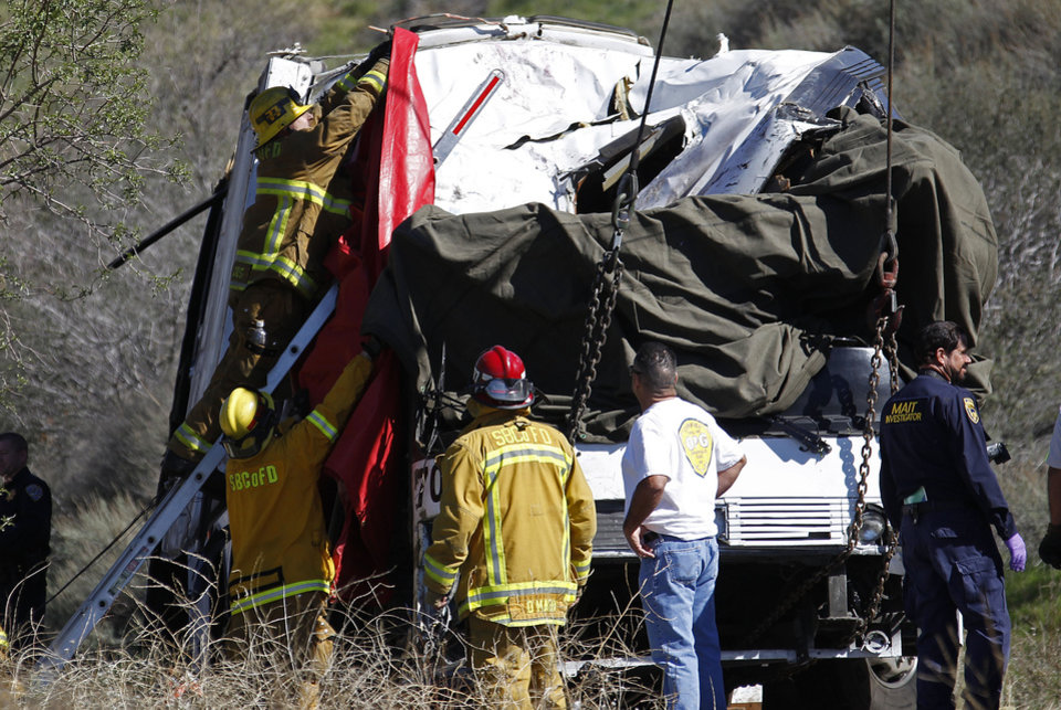 Photo - A firefighter adjusts a tarp to cover a victim inside after a tow truck lifted a tour bus back onto the road Monday, Feb. 4, 2013, after it collided with two other vehicles and crashed Sunday, killing at least eight people and injuring 38, on Highway 38 just north of Yucaipa, Calif.  The bus was carrying a tour group from Tijuana, Mexico.  (AP Photo/Reed Saxon)