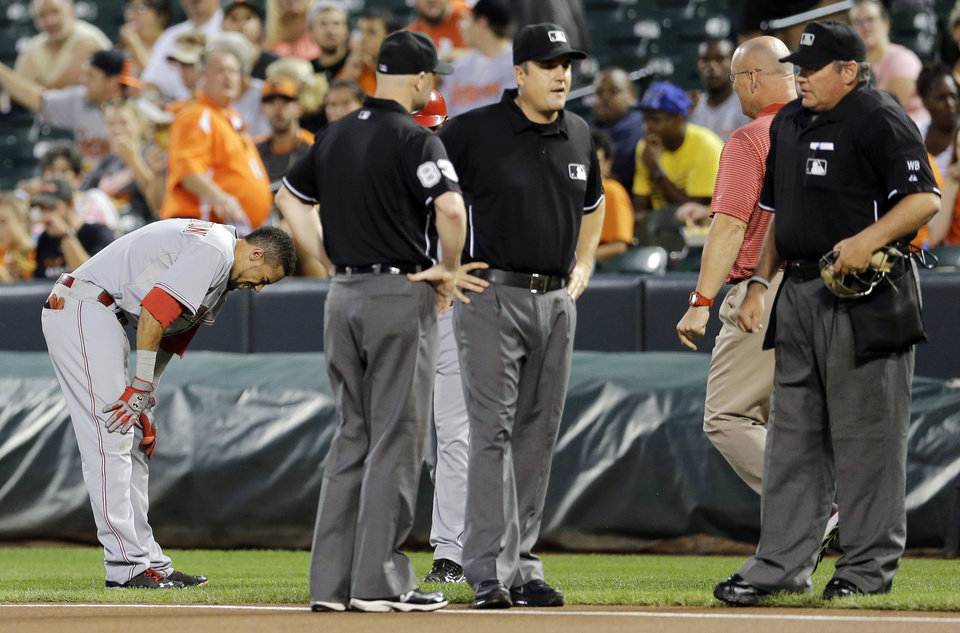 Photo - Cincinnati Reds' Billy Hamilton, left, pauses as umpires check on umpire Mike DiMuro, second from right, after the two collided in the first inning of an interleague baseball game, Tuesday, Sept. 2, 2014, in Baltimore. DiMuro left the field with a member of the Orioles athletic training staff after the play. (AP Photo/Patrick Semansky)