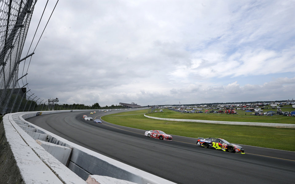 Photo - Jeff Gordon (24) leads Kyle Larson (42) through turn one during the NASCAR Sprint Cup Series auto race at Pocono Raceway, Sunday, Aug. 3, 2014, Long Pond, Pa. (AP Photo/Mel Evans)