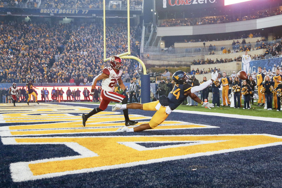 Photo - West Virginia Mountaineers wide receiver Dominique Maiden (82) dives to attempt to make catch a touchdown while being defend by Oklahoma Sooners safety Robert Barnes (20) during the NCAA football game between the Oklahoma Sooners and the West Virginia Mountaineers at Mountaineer Field at Milan Puskar Stadium in Morgantown, W.Va on Friday, November 23, 2018. IAN MAULE/Tulsa World