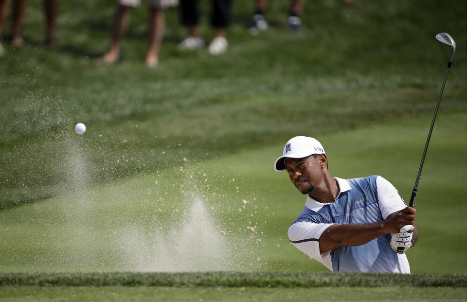 Photo - Tiger Woods hits out of the bunker on the seventh hole during a practice round for the PGA Championship golf tournament at Valhalla Golf Club on Wednesday, Aug. 6, 2014, in Louisville, Ky. The tournament is set to begin on Thursday. (AP Photo/David J. Phillip)
