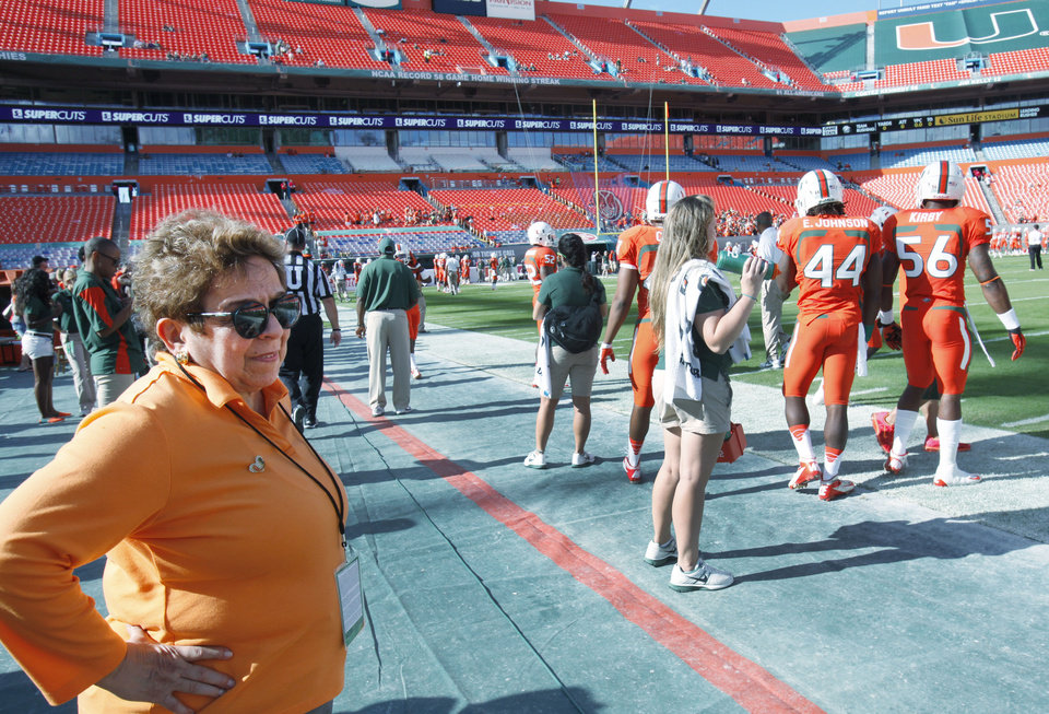 Photo - FILE - In this Nov. 17, 2012, file photo, Miami president Donna Shalala watches players during warmups before the start of an NCCA college football game between the Miami and the South Florida in Miami. Shalala would prefer Hurricane athletes get their degrees before leaving school, taking advantage of the scholarships they've been afforded. (AP Photo/Wilfredo Lee, File)