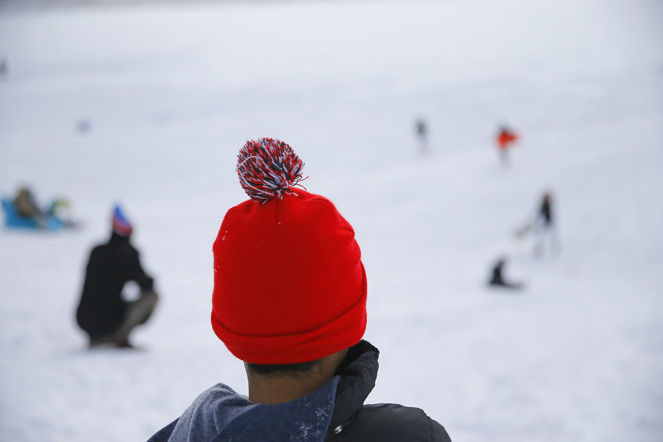 Photo - A child watches as sledder race down a hill along W Hefner Road in Oklahoma City after a winter storm dropped another layer of snow in Oklahoma City, Wednesday, Feb. 17, 2021. [Bryan Terry/The Oklahoman]