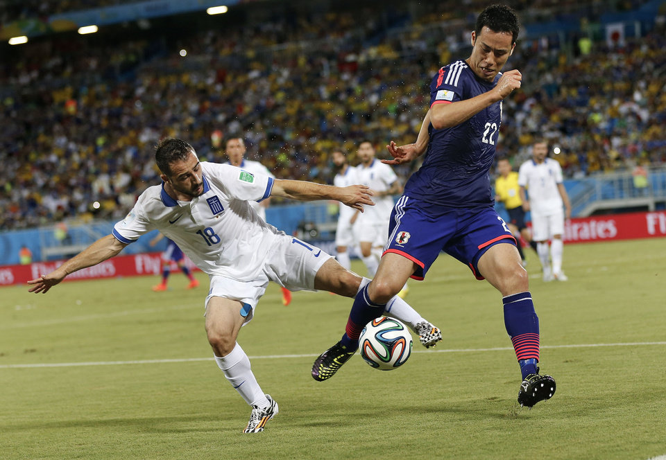 Photo - Greece's Giannis Fetfatzidis, left, challenges Japan's Maya Yoshida during the group C World Cup soccer match between Japan and Greece at the Arena das Dunas in Natal, Brazil, Thursday, June 19, 2014. (AP Photo/Frank Augstein)