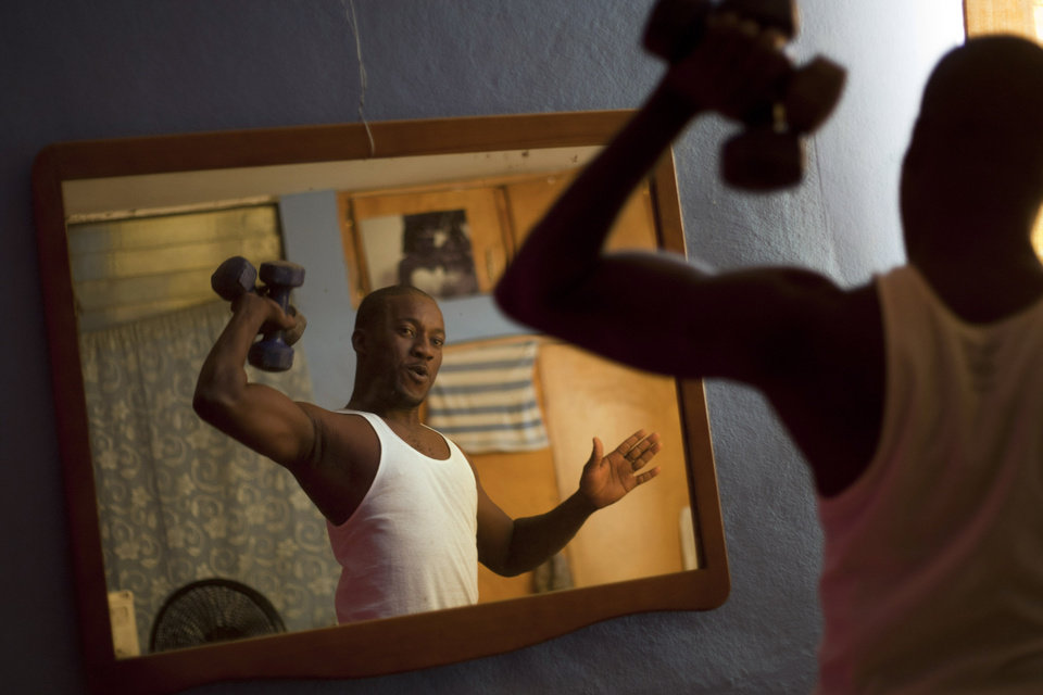 Photo - In this Jan. 18, 2013 photo, professional dancer Georges Exantus lifts weights in his bedroom in Port-au-Prince, Haiti.  Exantus thought he'd never dance again. The earthquake three years ago in Haiti's capital flattened the apartment where he was living, where he spent three days trapped under a heap of jagged rubble. After friends dug him out, doctors amputated his right leg just below the knee. Three years later, the 32-year-old professional dancer is back on the floor, spinning away as he does the salsa, cha-cha and samba. A prosthetic leg doesn't hold him back. If some see him as something of an outcast, his friends find inspiration: He's not one for self-pity; he was determined to dance again, and did. (AP Photo/Dieu Nalio Chery)