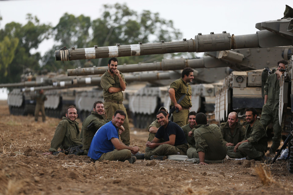 Photo - Israeli soldiers gather at a staging area on the Israel-Gaza border, Friday, July 11, 2014. Gaza rocket fire struck a gas station and set it ablaze Friday in southern Israel, seriously wounding one person as rocket fire also came from Lebanon for the first time in the four-day-long offensive. Rocket fire by Palestinian militants continued from Gaza toward various locations in southern Israel. (AP Photo/Lefteris Pitarakis)