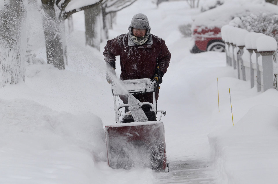 Photo - Kevin Pokorny works on his third house clearing snow for neighbors in Barrington, Ill., Thursday, Jan. 2, 2014. The New Year's Day snow storm stretched into Thursday for parts of Illinois, bringing double-digit snow totals to the suburbs of Chicago. (AP Photo/Daily Herald, Bob Chwedyk) MANDATORY CREDIT; MAGS OUT;  TV OUT