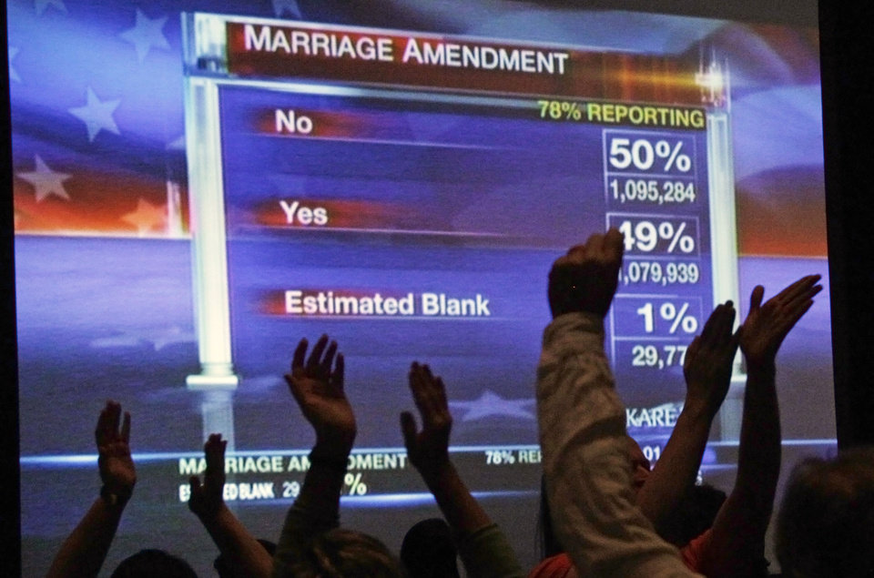 Photo -   Minnesotans United for All Families who oppose the gay marriage amendment cheer as the screen shows the