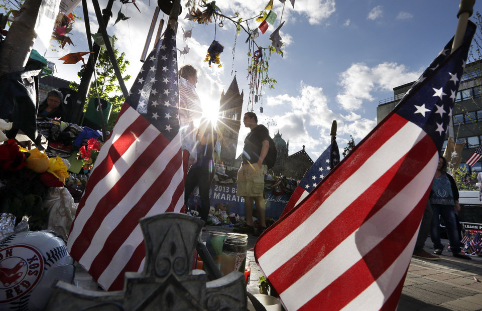 Photo - People walk through a makeshift memorial near the Boston Marathon finish line in Boston's Copley Square Tuesday, May 7, 2013, in remembrance of the Boston Marathon bombings. (AP Photo/Steven Senne)