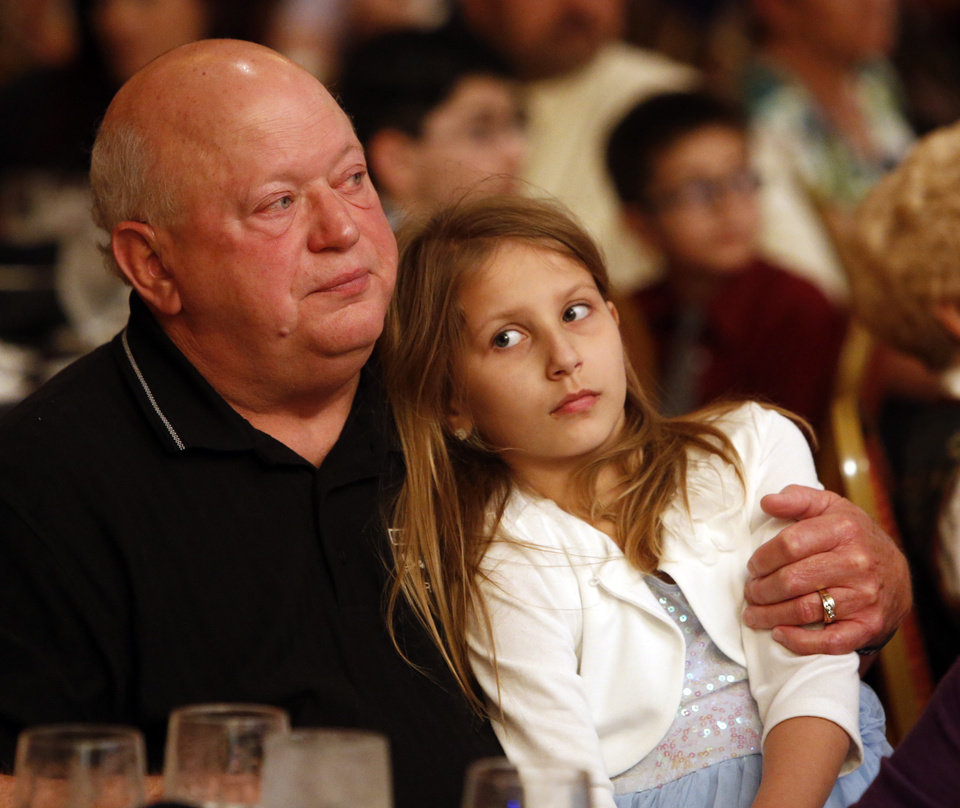 Photo - Bruce Dees and his granddaughter Claire, 8, listen as his son and her father Trooper Nicholas Dees is honored during the Trooper of the Year Awards on Wednesday in Norman. Photo by Steve Sisney, The Oklahoman  STEVE SISNEY - THE OKLAHOMAN