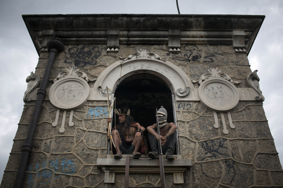 Photo - A man wearing a headdress and another wearing a ski mask sit on a windowsill on the site of an old Indian museum, in Rio de Janeiro, Brazil, Saturday, Jan. 12, 2013. Police in riot gear on Saturday surrounded the site in preparation for the eviction of an indigenous settlement of men and women living on the grounds of the old museum. The museum is located next to the Maracana stadium, which is being refurbished to host the opening and closing ceremonies of the 2016 Olympics and the final match of the 2014 World Cup. Authorities say the compound must go as the area around the stadium is also being refurbished, expected to be transformed into a shopping and sports entertainment hub. (AP Photo/Felipe Dana)