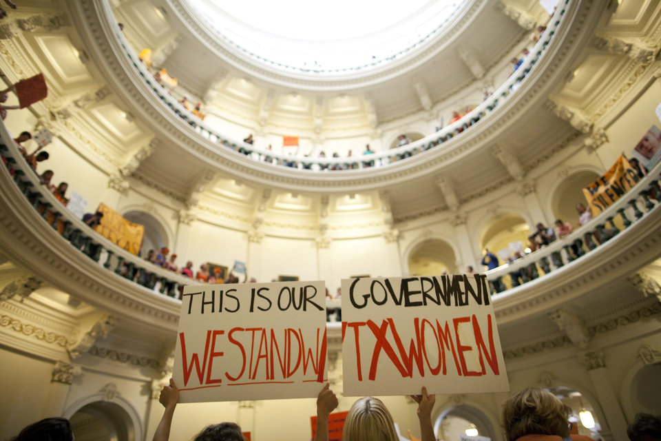 Photo - FILE - In this July 12, 2013 file photo, abortion rights supporters rally on the floor of the State Capitol rotunda in Austin, Texas. New abortion restrictions passed by the Texas Legislature are unconstitutional and will not take effect as scheduled on Tuesday, Oct. 29, 2013, a federal judge has ruled. (AP Photo/Tamir Kalifa, File)