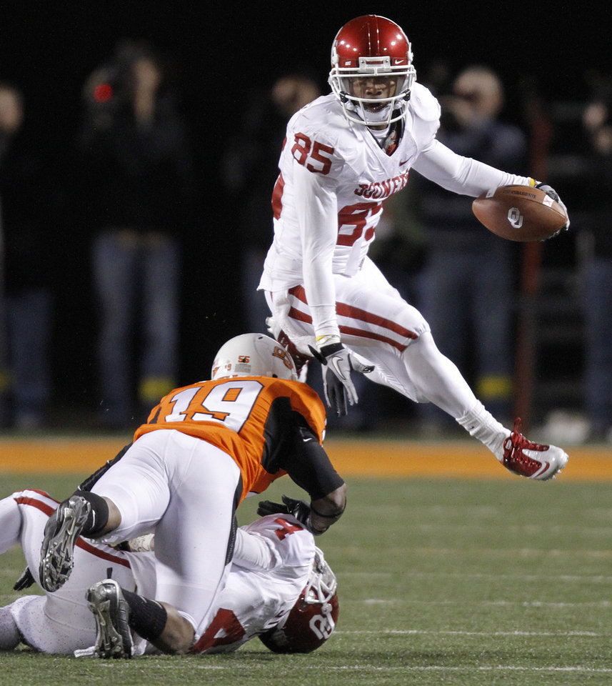 Photo - Oklahoma's Ryan Broyles (85) leaps over Oklahoma State's Brodrick Brown (19) during the Bedlam college football game between the University of Oklahoma Sooners (OU) and the Oklahoma State University Cowboys (OSU) at Boone Pickens Stadium in Stillwater, Okla., Saturday, Nov. 27, 2010. Photo by Chris Landsberger, The Oklahoman
