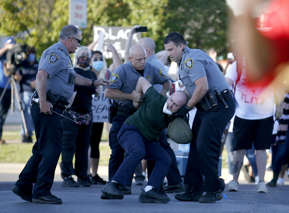 Photo - Oklahoma City police officers arrest a protester during a protest in the intersection of 23rd and Classen in Oklahoma City, Saturday, May 30, 2020. The protest was in response to the death of George Floyd. [Sarah Phipps/The Oklahoman]