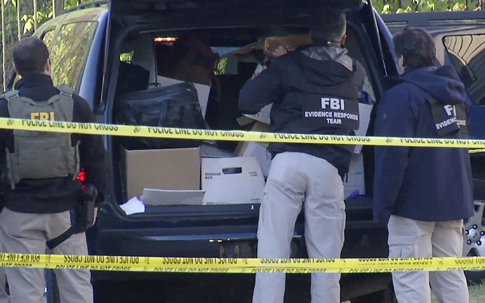 Photo - In this photo taken from video, FBI agents collect evidence at an apartment in Atlanta, Thursday morning, April 10, 2014, where federal agents rescued kidnap victim Frank Arthur Janssen, of Wake Forest. N.C. John Strong, FBI special agent in charge in North Carolina, said the kidnapping of Janssen was related to his daughter's prosecution of North Carolina prisoner Kelvin Melton, who is serving a life sentence for his 2012 conviction for being a habitual felon. (AP Photo/Johnny Clark)