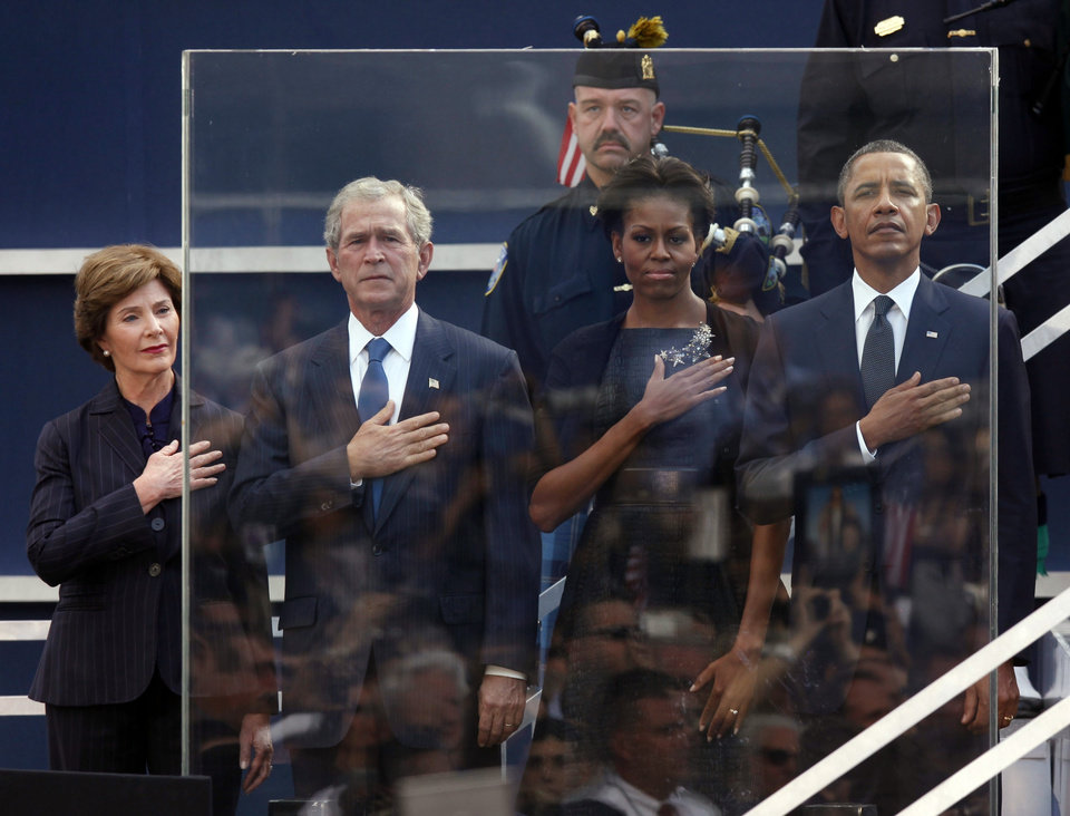 Photo -   Former first lady Laura Bush, from left, former President George W. Bush, first lady Michelle Obama and President Barack Obama hold hands to their hearts during the national anthem as friends and relatives of the victims of 9/11 gather for a ceremony marking the 10th anniversary of the attacks at the National September 11 Memorial at the World Trade Center site, Sunday, Sept. 11, 2011, in New York. (AP Photo/Jason DeCrow)