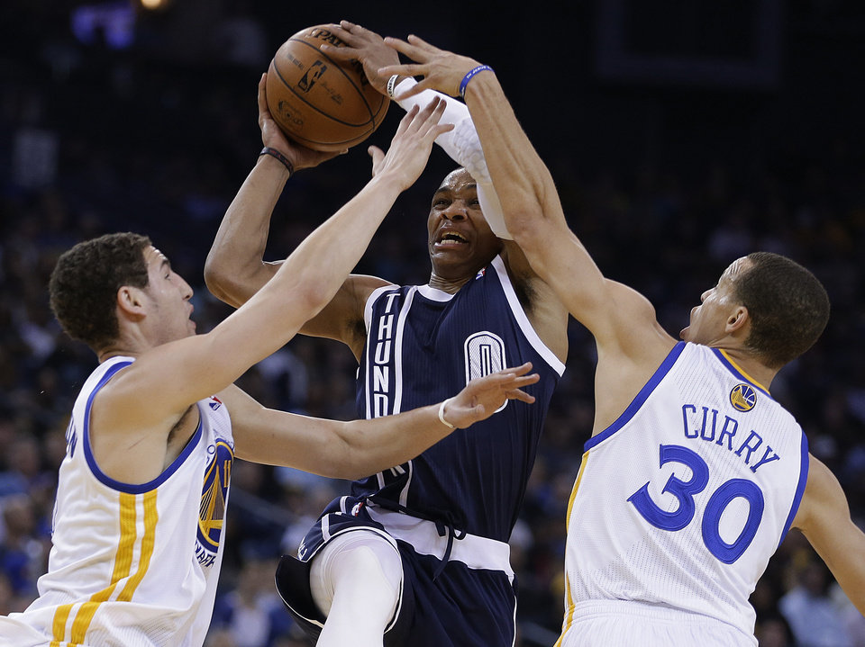 Oklahoma Thunder guard Russell Westbrook (0) shoots between Golden State Warriors' Klay Thompson, left, and Stephen Curry (30) during the first half of an NBA basketball game Thursday, April 11, 2013, in Oakland, Calif. (AP Photo/Ben Margot) ORG XMIT: OAS101