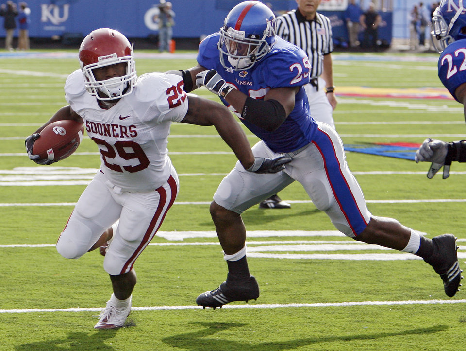 Photo - Kansas' Darrell Stuckey (25) stops Oklahoma's Chris Brown (29) just short of the goal line during the first half of the college football game between the University of Oklahoma Sooners (OU) and the University of Kansas Jayhawks (KU) on Saturday, Oct. 24, 2009, in Lawrence, Kan. Photo by Chris Landsberger, The Oklahoman