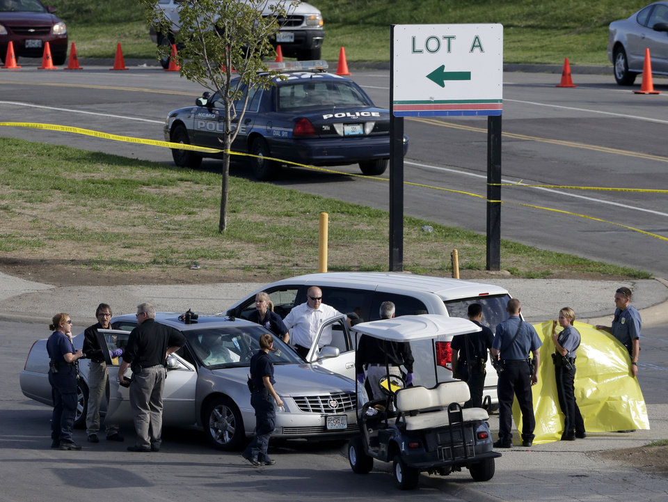 Photo -   Kansas City police investigate the scene of a shooting and apparent suicide in a parking lot outside Kauffman Stadium before a Kansas City Royals baseball game Friday, Sept. 14, 2012, in Kansas City, Mo. According to witnesses, the man driving the silver Cadillac fired several shots wounding a female parking attendant before turning the gun on himself. (AP Photo/Charlie Riedel)