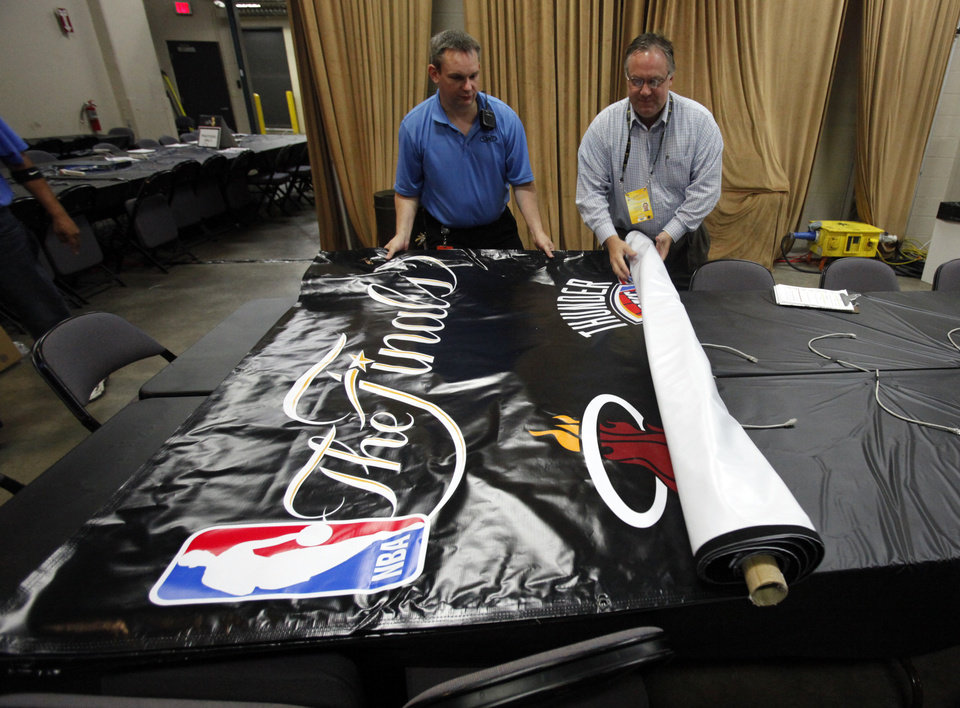 Operations Manager Chris Chartier gets posters to display from NBA official Patrick Mahoney at 7:30 am as SMG personnell make final preparations for the first game of the NBA basketball finals at the Chesapeake Arena on Tuesday, June 12, 2012 in Oklahoma City, Okla.  Photo by Steve Sisney, The Oklahoman