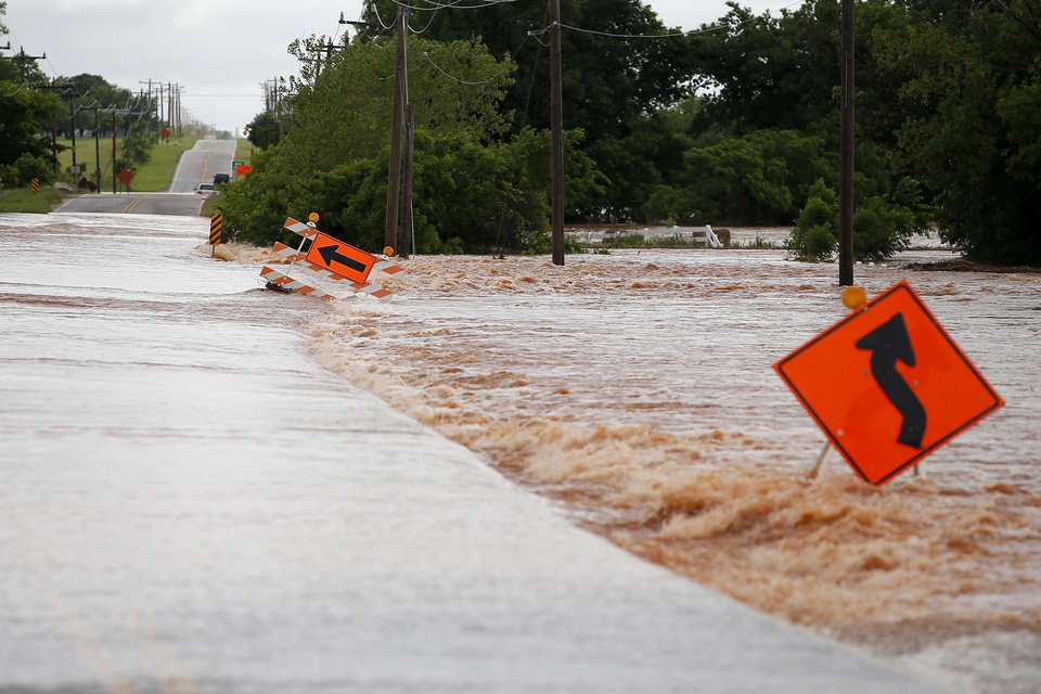 Photo - Floodwaters carry a road sign off the road on NW 206 just west of Portland in Oklahoma City, Tuesday, May 21, 2019. [Bryan Terry/The Oklahoman]