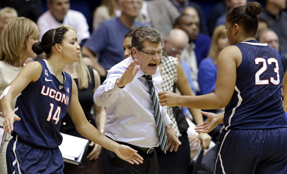 Photo - Connecticut's Bria Hartley (14) and coach Geno Auriemma congratulate Kaleena Mosqueda-Lewis (23) as Mosqueda-Lewis leaves the court during the second half of an NCAA college basketball game against  Duke in Durham, N.C., Tuesday, Dec. 17, 2013. Connecticut won 83-61.(AP Photo/Gerry Broome)