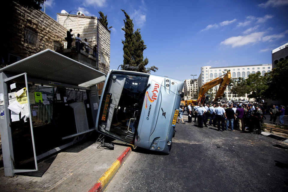 Photo - A damaged bus flipped over after attack in Jerusalem, Monday, Aug. 4, 2014. An Israeli-declared cease-fire and troop withdrawals slowed violence in the Gaza war Monday, though an attack on Israeli bus that killed one person in Jerusalem underscored the tensions still simmering in the region. (AP Photo/Sebastian Scheiner)