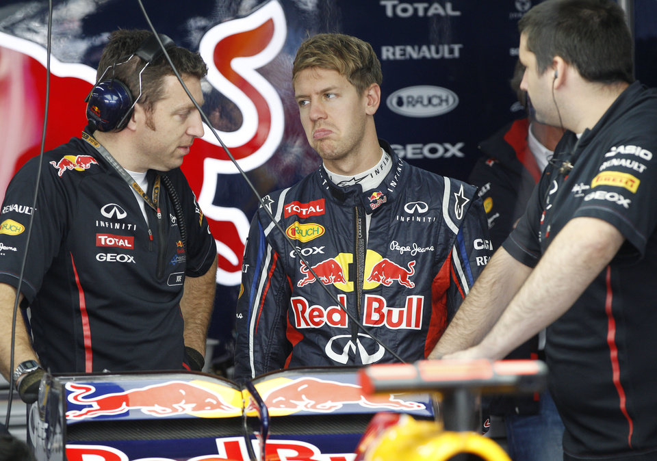 Photo -   Red Bull driver Sebastian Vettel, centre, of Germany talks with his mechanics during the first practice session for the Korean Formula One Grand Prix at the Korean International Circuit in Yeongam, South Korea, Friday, Oct. 12, 2012. (AP Photo/Dita Alangkara)