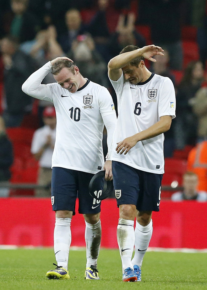 Photo - England's Wayne Rooney, left, and Phil Jagielka gesture after the World Cup Group H qualification soccer match between England and Poland at Wembley stadium in London, Tuesday, Oct. 15, 2013.   England won the match 2-0 and qualify for the 2014 World Cup in Brazil. (AP Photo/Matt Dunham)