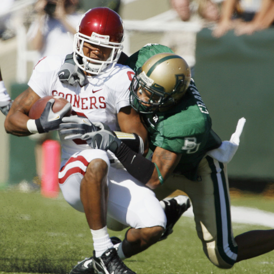 Photo - Juaquin Iglesias is pulled down by Dwain Crawford (1) in the first half during the University of Oklahoma Sooners (OU) college football game against Baylor University Bears (BU) at Floyd Casey Stadium, on Saturday, Nov. 18, 2006, in Waco, Texas.     by Steve Sisney, The Oklahoman