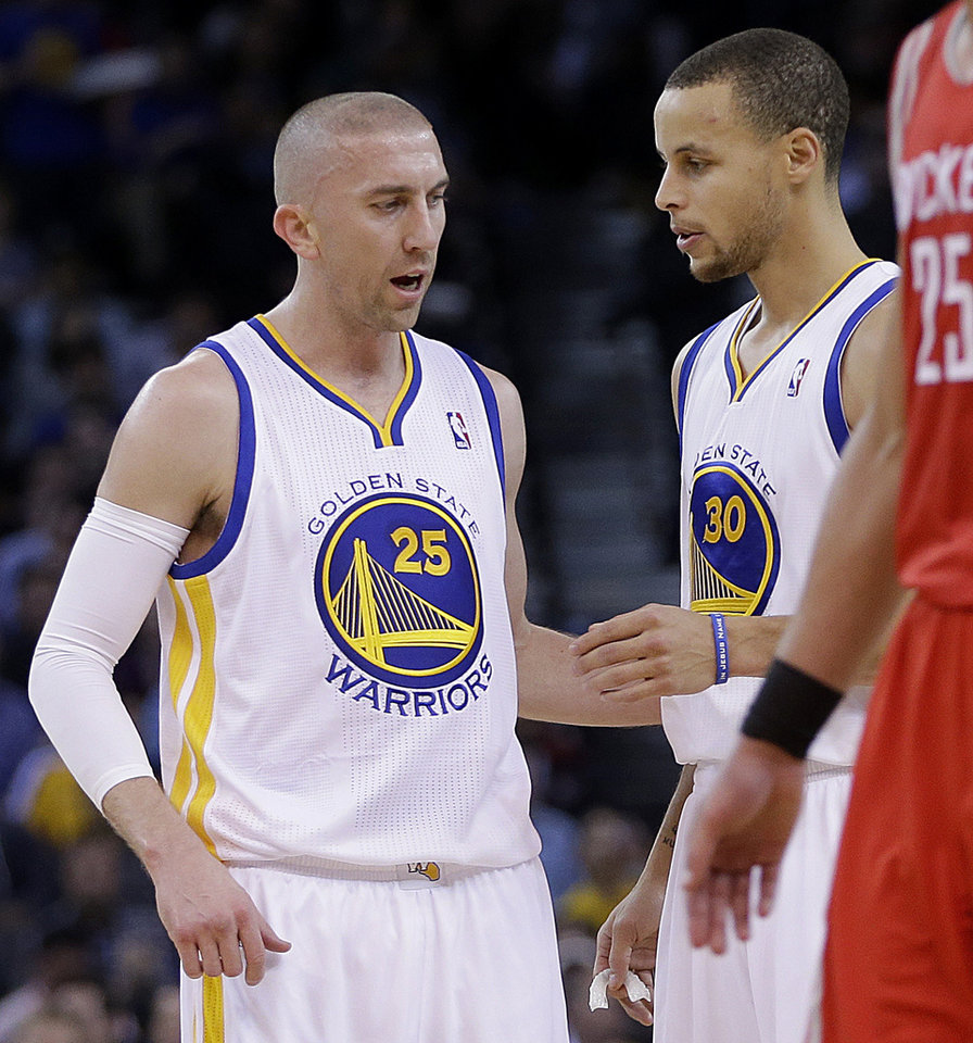 Photo - Golden State Warriors' Steve Blake, left, speaks with Stephen Curry (30) during the first half of an NBA basketball game against the Houston Rockets on Thursday, Feb. 20, 2014, in Oakland, Calif. (AP Photo/Ben Margot)