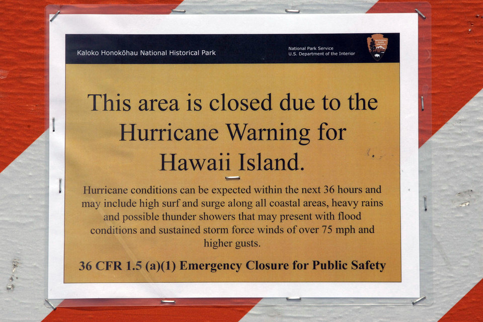 Photo - A hurricane warning sign is shown posted on the beach in Kailua, Hawaii, Thursday, Aug. 7, 2014., as the area prepares for Hurricane Iselle. Hurricane Iselle is expected to arrive on the Big Island on Thursday evening, bringing heavy rains, winds gusting up to 85 mph and flooding in some areas. Weather officials changed their outlook on the system Wednesday after seeing it get a little stronger, giving it enough oomph to stay a hurricane as it reaches landfall. (AP Photo/Chris Stewart)