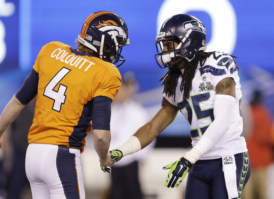 Photo - Denver Broncos' Britton Colquitt (4) talks with Seattle Seahawks' Richard Sherman (25) before the NFL Super Bowl XLVIII football game Sunday, Feb. 2, 2014, in East Rutherford, N.J. (AP Photo/Jeff Roberson)