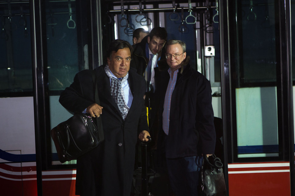 Photo - Former New Mexico Gov. Bill Richardson, left, and Executive Chairman of Google, Eric Schmidt, disembark from an airport transfer bus after arriving at Pyongyang International Airport in Pyongyang, North Korea on Monday, Jan. 7, 2013. Richardson called the trip to North Korea a private humanitarian visit. In the background is Google Ideas think tank director, Jared Cohen. (AP Photo/David Guttenfelder)
