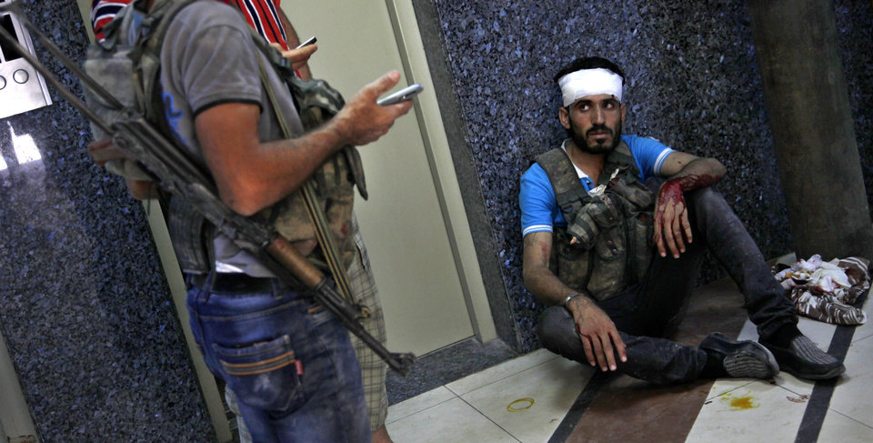 Photo -   An injured Syrian fighter sits on the ground after being treated at a field hospital in Aleppo, Syria, Friday, Aug. 17, 2012. Rebel footholds in Aleppo have been the target of weeks of Syrian shelling and air attacks as part of wider offensives by President Bashar Assad's regime. Rebels have been driven from some areas, but the report of clashes near the airport suggests the battles could be shifting to new fronts. (AP Photo/ Khalil Hamra)