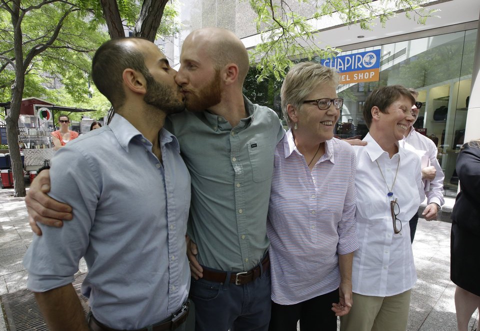 Photo - From left, Moudi Sbeity and Derek Kitchen kiss accompanied by fellow plaintiffs Laurie Wood and Kody Partridge at a news conference outside their lawyer's office in Salt Lake City on Wednesday, June 25, 2014. On Wednesday, a federal appeals court in Denver ruled that states must allow gay couples to marry, finding the Constitution protects same-sex relationships. The decision from a three-judge panel in Denver upheld a lower court ruling that struck down Utah's gay marriage ban which the couples fought. (AP Photo/Rick Bowmer)