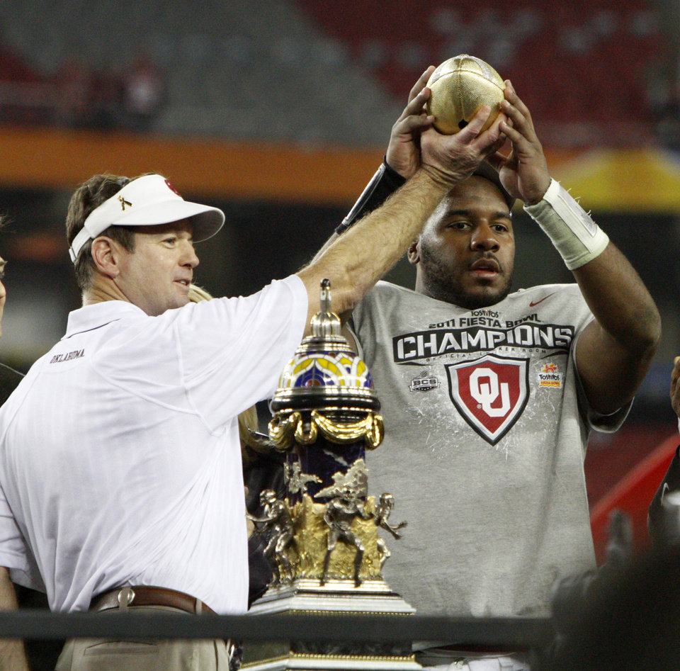 Photo - OU coach Bob Stoops hands part of the trophy to Oklahoma's Jeremy Beal (44) after the Fiesta Bowl college football game between the University of Oklahoma Sooners and the University of Connecticut Huskies in Glendale, Ariz., at the University of Phoenix Stadium on Saturday, Jan. 1, 2011.  Photo by Bryan Terry, The Oklahoman