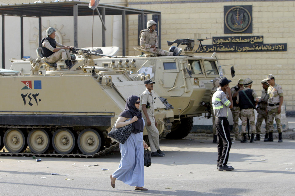 Photo - An Egyptian walks in front of armored vehicles guarding Torah Prison, where ousted President Hosni Mubarak is held in Cairo, Egypt, Wednesday, Aug. 21, 2013. An Egyptian court ordered Wednesday the release of ousted President Hosni Mubarak, but it is not yet clear if the ailing ex-leader will walk free after over two years in detention, officials said. The prospects of Mubarak's release after the 2011 uprising against him, and a slew of court cases that made him the first Arab leader to be tried by his own people, are likely to further fuel the rest that has hit Egypt following the military coup against his successor, the first freely elected president Islamist Mohammed Morsi. (AP Photo/Amr Nabil)
