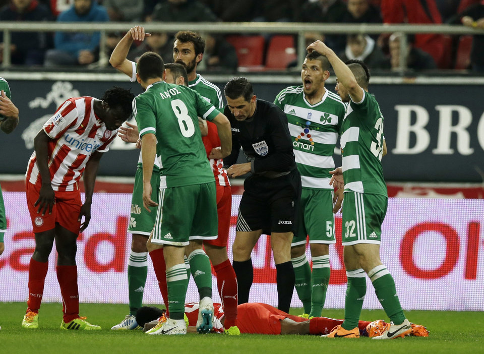 Photo - Olympiakos' Michael Olaitan of Nigeria lays on the pitch as Panathinaikos' players call for a medic during a Greek League soccer match at Georgios Karaiskakis stadium, in Piraeus port, near Athens, on Sunday, March 2, 2014. Olaitan collapsed suddenly when walking alone on the field and hit his head upon falling. He was carried away,on a stretcher and taken to a hospital for tests. (AP Photo/Thanassis Stavrakis)