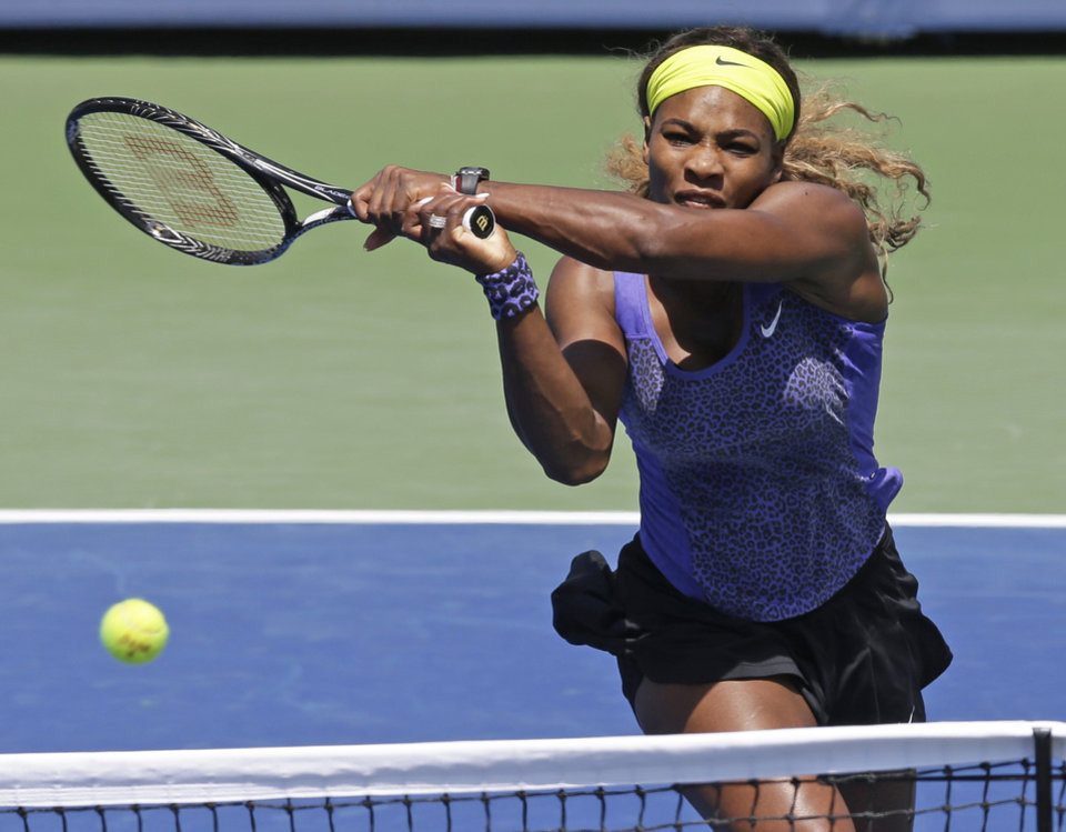 Photo - Serena Williams volleys against Jelena Jankovic, from Serbia, during a match at the Western & Southern Open tennis tournament, Friday, Aug. 15, 2014, in Mason, Ohio. (AP Photo/Al Behrman)