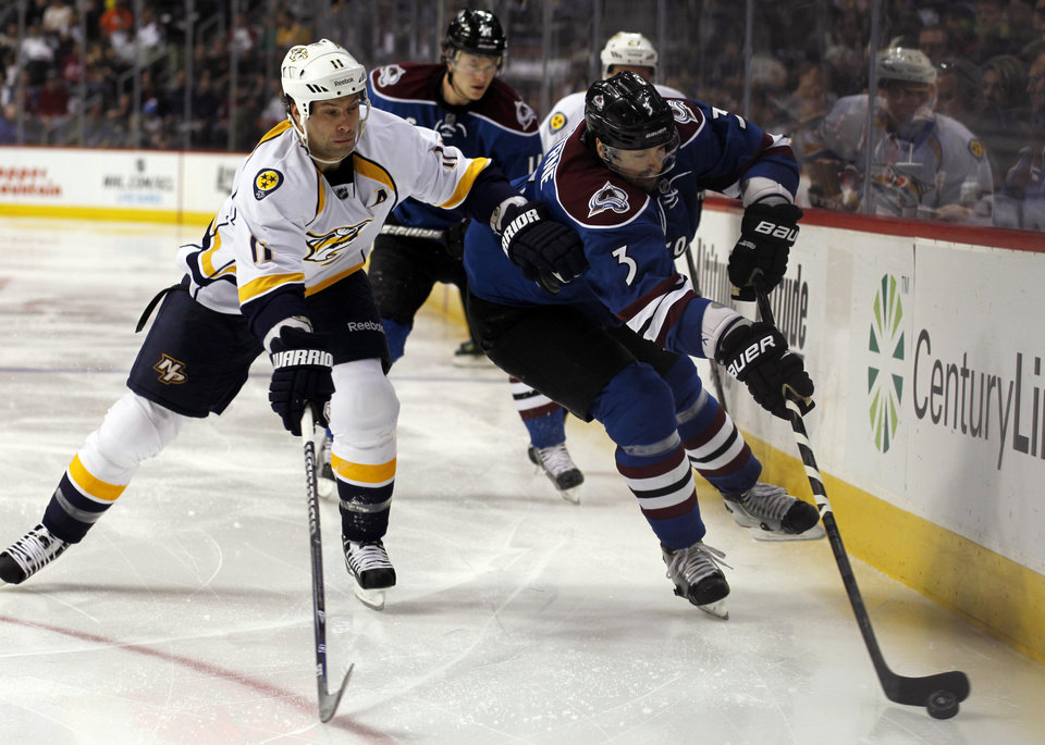 Colorado Avalanche defenseman Ryan O'Byrne, right, picks up a loose puck along the boards as Nashville Predators right wing Martin Erat, of the Czech Republic, covers in the second period of an NHL hockey game in Denver, Saturday, March 30, 2013. (AP Photo/David Zalubowski)