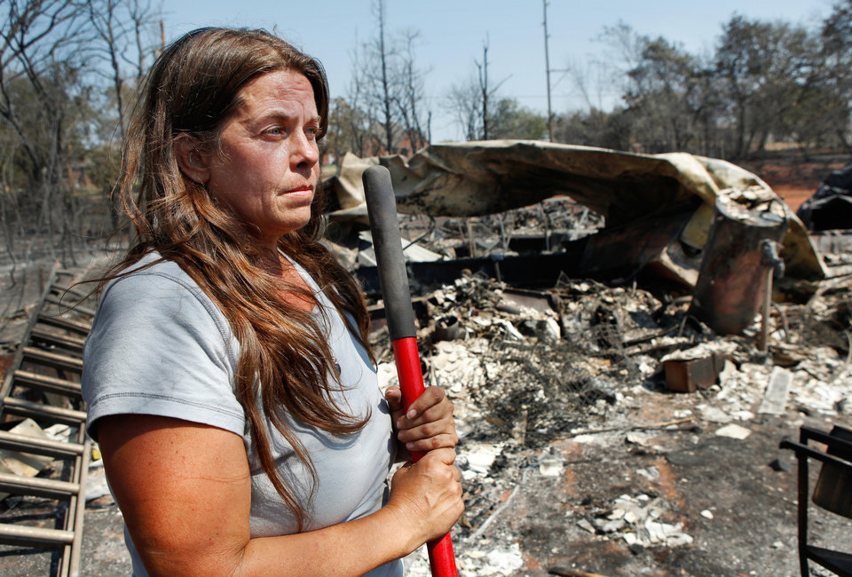 Photo - Her face dirtied from the mixture of sweat and ashes, Lori Turner holds the handle of a rake as she pauses from combing through the charred rubble of her mobile home on her property at 6000 NE 63 Wednesday after wildfires ravaged land and property that stretched from NE 50 on the south to Hefner Road on the north.  Turner said she lost everything she had in this fire.